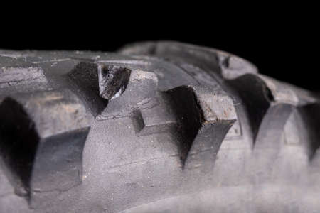 Damaged tread in a motocross tire. Damaged tire with high tread. Dark background.