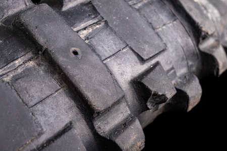Hole in the tire from a motorcycle. Damaged tire with high tread. Dark background.
