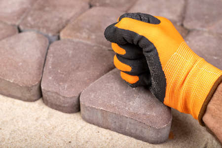 Laying paving stones on sand. Concrete cube in the hand of a builder. Light background.