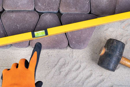 Laying paving stones on sand. A spirit level for measuring in construction. Light background.