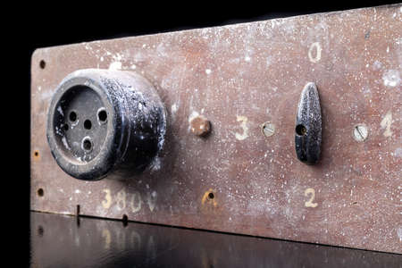 Old high voltage electric socket. Electric board with a controller. Dark background. Standard-Bild