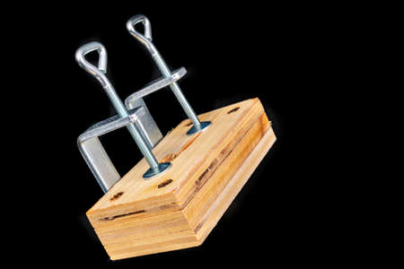 Bonding two pieces of raw plywood in carpentry clamps. Minor carpentry work in a home workshop. Dark background. Standard-Bild