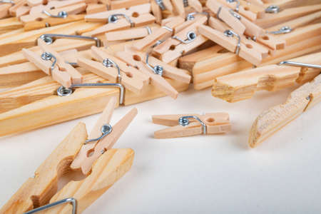 Small and large wooden clothes pegs. Household accessories. White background.