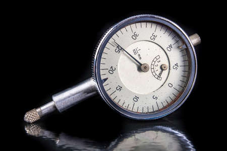 Dial gauge for measurement in the metal industry. Accessories for markers and quality controllers. Dark background.