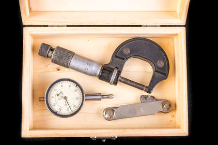 Measuring tools in a wooden case. Accessories for markers and quality controllers. Dark background.