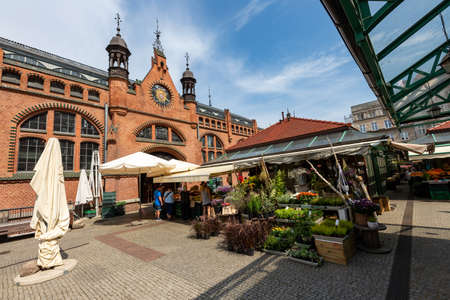 Gdansk, pomorskie / Poland - August, 8, 2020: Historic market hall in Gdansk. Historic tenement houses in the city of Central Europe. Summer season.