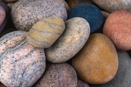 Dry oval stones found on the seashore. Stones carved by sea water. Dark background.