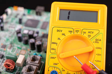 Voltmeter and circuit board. Measurements and repairs in an electronics workshop. Dark background.