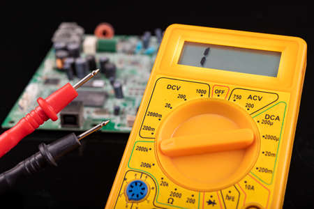 Voltmeter and circuit board. Measurements and repairs in an electronics workshop. Dark background. Imagens