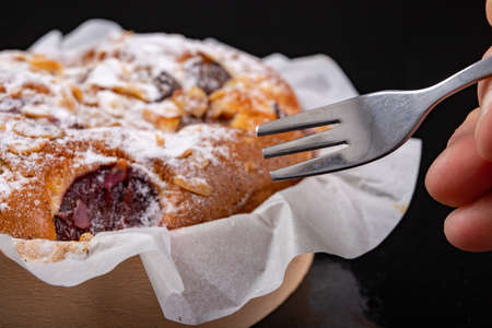 Tasty fruit pie in a paper mold and fork. Dessert prepared for serving. Dark background. 版權商用圖片