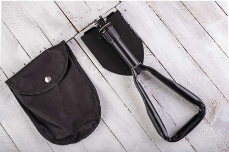 Black military shovel on a wooden table. Military accessories for excavating anti-personnel mines. White background.