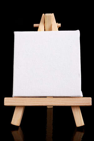 Small easel with white blank cloth on a wooden table. Miniature painting accessories. Dark background.