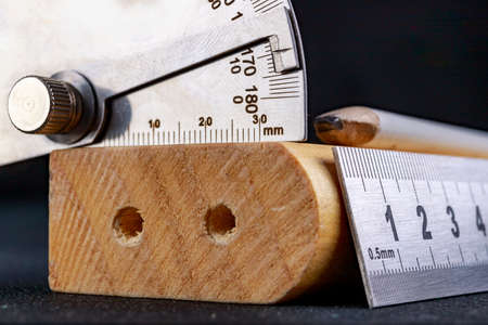 A protractor and a metal ruler to measure angles in a carpentry workshop. Accessories for measuring and drawing in a carpentry shop. Workplace - workshop.