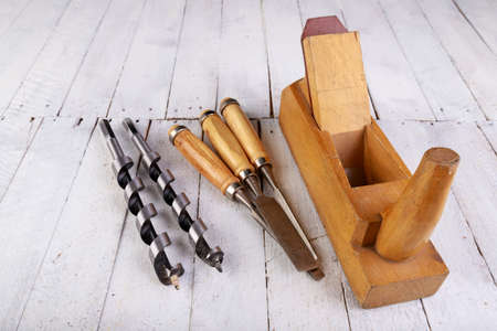 Wood planer, chisels and drill bits on a wooden table. Carpentry accessories in a home workshop. Light background.