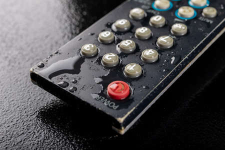 TV remote control with water drops. Water-poured electronic device. Dark background.
