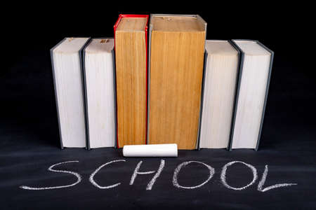 A row of paper books arranged under the word school. School blackboard and thick training books. Dark background.