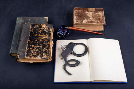 Handcuffs and a notebook on the table. Accessories on the desk at the police station. Dark background.