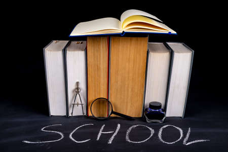 A row of paper books stacked over the word school. School accessories blackboard and thick training books. Dark background.