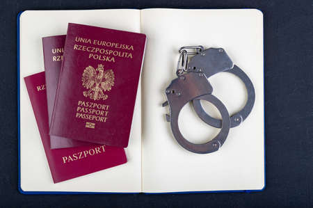 Handcuffs, passport and notebook on the table. Accessories on the desk at the police station . Dark background.