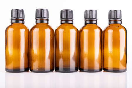 Small glass bottles for the storage of light-sensitive liquids. Containers used in pharmaceuticals. Light background. Archivio Fotografico