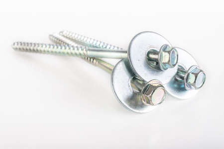Long nickel-plated wood screws with washers. Metal accessories for joining wooden elements. Light background.