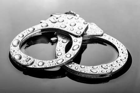 Water drops on metal handcuffs. Police accessories to incapacitate people flooded with water. Dark background.