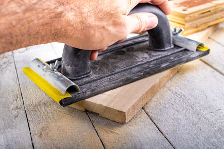 Sanding wood with sandpaper. Carpentry accessories for precise woodworking. Light background.