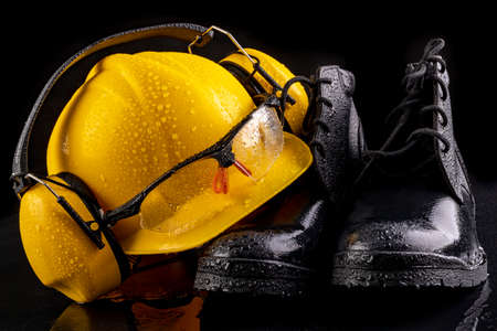 Wet workwear for a production worker. Raindrops on the helmet and glasses. Dark background. Archivio Fotografico