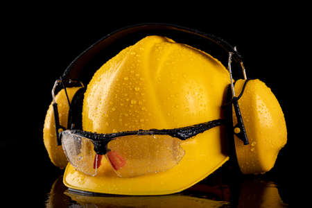 Wet work helmet and safety glasses. Raindrops on health and safety accessories for construction workers. Dark background.