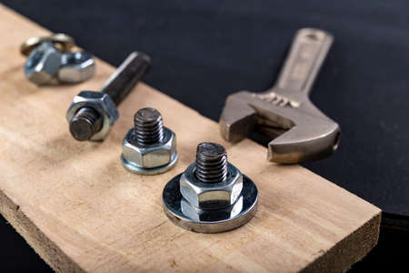 Metal bolts and nuts for joining wood. Tightening the screws with an adjustable wrench. Dark background. Archivio Fotografico