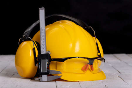 A helmet and protective glasses on a workbench. Caliper for work in a home workshop. Dark background.