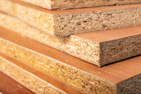 Particle board for the construction of home furniture. Material stacked in the carpentry shop. Light background. Stock Photo