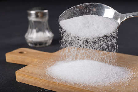 Sprinkling salt from a metal spoon. A flavor enhancer added to dishes in home cooking. Dark background.