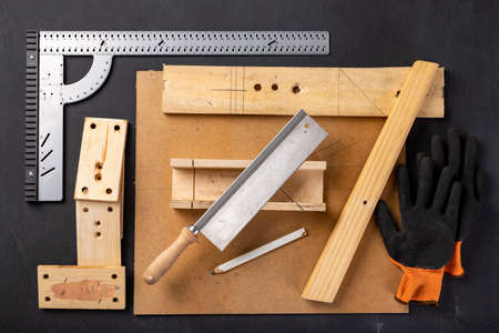 A table in a home carpentry workshop. Woodworking accessories at the carpenter's stand. Dark background.
