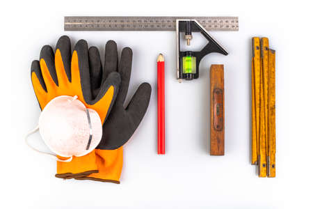 Gloves, tape measure and pencil for carpentry work. Carpentry accessories used in the workshop. Light background.