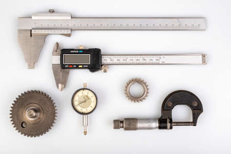 Accessories for accurate measurements in the engineering laboratory. Caliper and micrometer for measuring work. Light background.