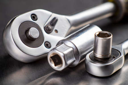 Chrome ratchet wrenches on the workbench. Tools used for mechanical repairs. Workshop workplace.