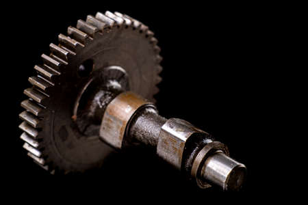 Camshaft from a small internal combustion engine. Accessories for repairing drive systems. Dark background.
