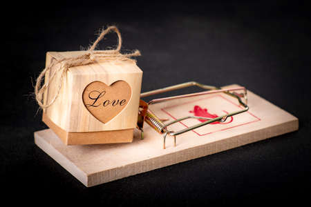 A box with the word love placed in a mousetrap. Love for a person with bad intentions. Dark background.