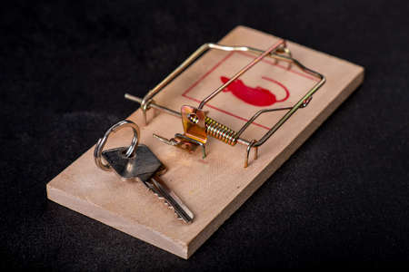 The key to the apartment is placed in a mousetrap. The trap of wrong real estate purchase. Dark background.