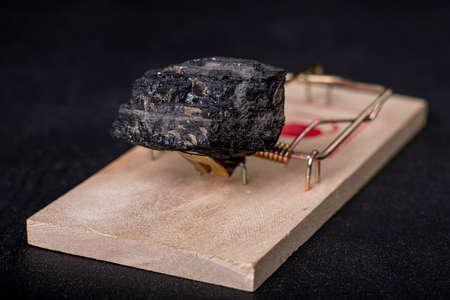 A black lump of brown coal placed in a mousetrap. A trap in the form of coal used to obtain energy. Dark background. Standard-Bild