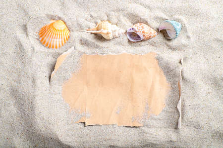 Gray blank paper covered with sand and seashells. A letter stacked on the beach. Summer season.