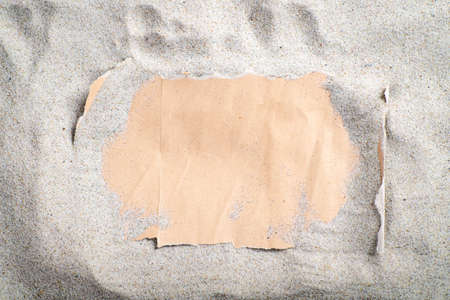 Gray blank paper covered with sand. A letter stacked on the beach. Summer season.