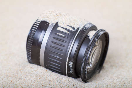 The camera lens is covered with sea sand. Optical accessories subject to harsh working conditions. Summer season.