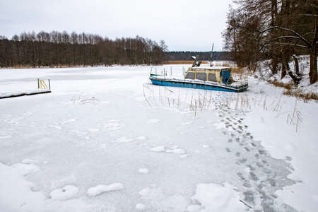 A large boat trapped in ice on a lake. A frozen lake in a boat dock. Winter season.