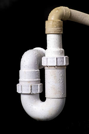 Hydraulic wet siphon for a wash basin. Accessories and spare parts for plumbers who renovate water and sewage systems. Black background.