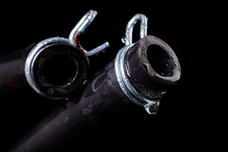 Wet black hose with metal clamp. Accessories and spare parts for plumbers who renovate water and sewage systems. Black background.
