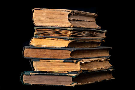 A stack of old books. Paper publications from the old library. Dark background.