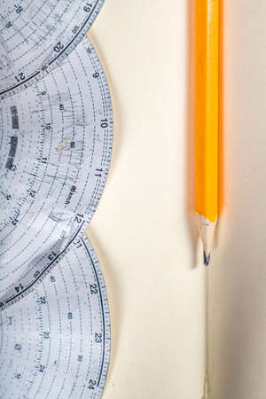 Tachograph chart and pencil for recording the time and mileage of a truck. Route, driver and vehicle identification data. Light background.