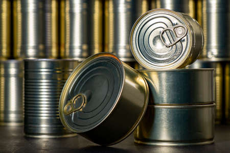 Metal cans with preserved meat. Food with a long shelf life. Dark background.